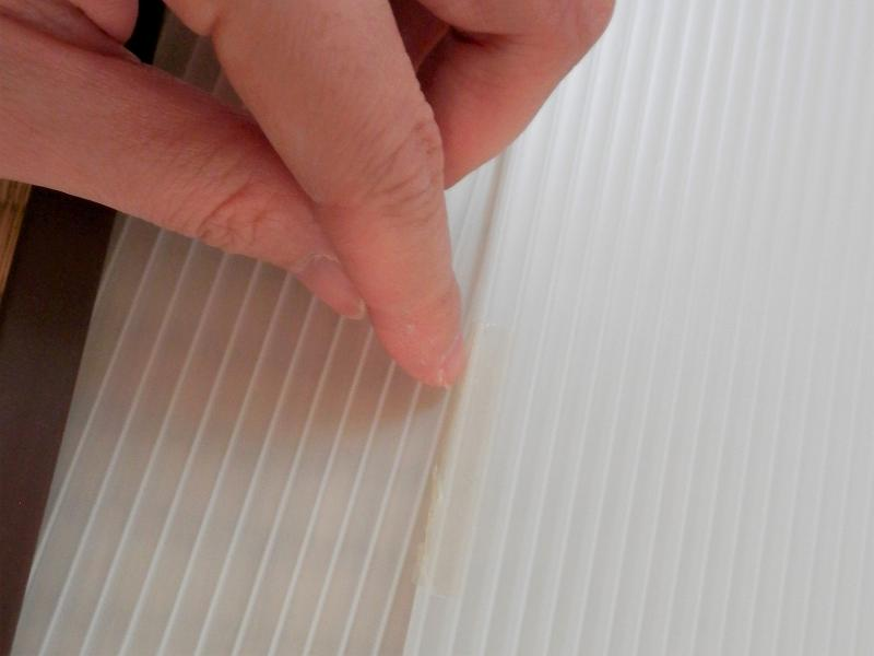 プラダンに貼った両面テープの縁を押さえる