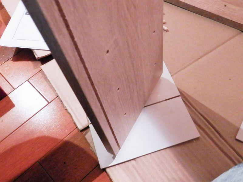 棚板の下に梱包材の板を敷いてる様子(3連本棚)