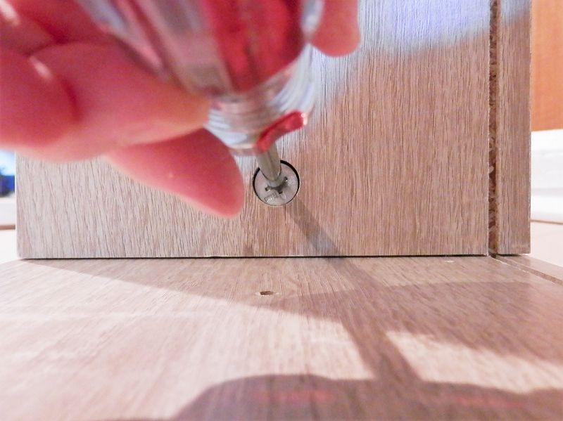 固定棚板の金属部品を締め上げる(3連本棚)
